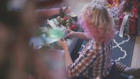 Γυναίκα με τα σγουρά άσπρα και ρόδινα χριστουγεννιάτικα δώρα πακέτων τρίχας απόθεμα βίντεο