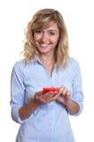 Γυναίκα με τα σγουρά ξανθά μαλλιά που στέλνουν το μήνυμα με το τηλέφωνο Στοκ Εικόνα