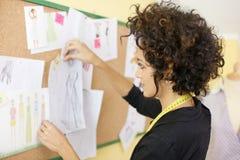 Γυναίκα με τα σκίτσα στο στούντιο σχεδίου μόδας Στοκ εικόνες με δικαίωμα ελεύθερης χρήσης