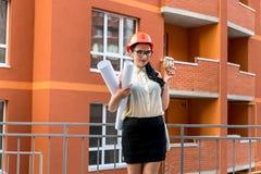 Γυναίκα με τα σχεδιαγράμματα και πρότυπο σπιτιών στην οικοδόμηση στοκ φωτογραφία με δικαίωμα ελεύθερης χρήσης