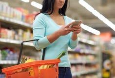 Γυναίκα με τα τρόφιμα αγοράς smartphone στην υπεραγορά Στοκ Εικόνες