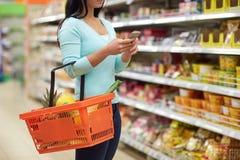 Γυναίκα με τα τρόφιμα αγοράς smartphone στην υπεραγορά Στοκ φωτογραφία με δικαίωμα ελεύθερης χρήσης