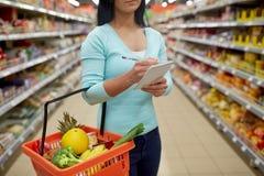 Γυναίκα με τα τρόφιμα στο καλάθι αγορών στην υπεραγορά στοκ εικόνα με δικαίωμα ελεύθερης χρήσης