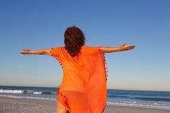 Γυναίκα με τα όπλα που τεντώνονται να ξεχωρίσει στην παραλία στην ηλιοφάνεια στοκ φωτογραφίες