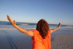 Γυναίκα με τα όπλα που τεντώνονται να ξεχωρίσει στην παραλία στην ηλιοφάνεια στοκ φωτογραφία με δικαίωμα ελεύθερης χρήσης