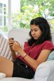 Γυναίκα με την έξυπνη τηλεφωνική συνεδρίασή της στον καναπέ στο καθιστικό Στοκ Φωτογραφίες