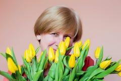 Γυναίκα με την ανθοδέσμη των κίτρινων τουλιπών που χαμογελούν μυστιριωδώς, γέννηση στοκ φωτογραφία