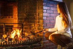 Γυναίκα με την εστία πόκερ σιδήρου πυρκαγιάς στο σπίτι Στοκ Φωτογραφίες