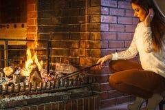 Γυναίκα με την εστία πόκερ σιδήρου πυρκαγιάς στο σπίτι Στοκ φωτογραφίες με δικαίωμα ελεύθερης χρήσης