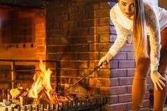 Γυναίκα με την εστία πόκερ σιδήρου πυρκαγιάς στο σπίτι Στοκ Εικόνες