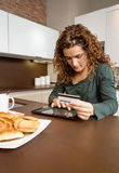 Γυναίκα με την ηλεκτρονική πιστωτική κάρτα αναθεώρησης ταμπλετών Στοκ Φωτογραφία