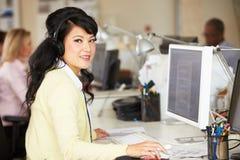Γυναίκα με την κάσκα που λειτουργεί στο γραφείο στο απασχολημένο δημιουργικό γραφείο Στοκ Φωτογραφία
