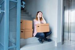 Γυναίκα με την κίνηση των κιβωτίων που κάθονται στα σκαλοπάτια στο εσωτερικό Στοκ Εικόνες