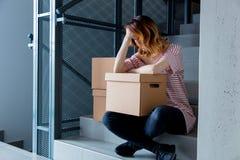 Γυναίκα με την κίνηση των κιβωτίων που κάθονται στα σκαλοπάτια στο εσωτερικό Στοκ εικόνα με δικαίωμα ελεύθερης χρήσης