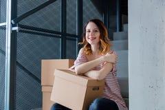Γυναίκα με την κίνηση των κιβωτίων που κάθονται στα σκαλοπάτια στο εσωτερικό Στοκ φωτογραφία με δικαίωμα ελεύθερης χρήσης