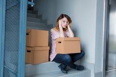 Γυναίκα με την κίνηση των κιβωτίων που κάθονται στα σκαλοπάτια στο εσωτερικό Στοκ Φωτογραφίες