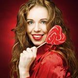Γυναίκα με την καραμέλα καρδιών πέρα από το κόκκινο υπόβαθρο Στοκ Εικόνες