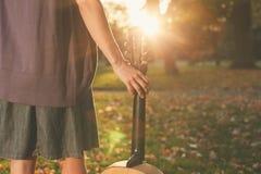 Γυναίκα με την κιθάρα στο ηλιοβασίλεμα στο πάρκο Στοκ Φωτογραφία
