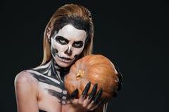 Γυναίκα με την κολοκύθα εκμετάλλευσης αποκριών σκελετών makeup Στοκ Εικόνα