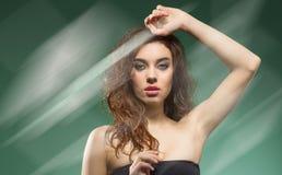 Γυναίκα με την κυματιστή τρίχα στον ώμο σε πράσινο στοκ φωτογραφίες