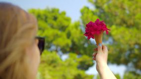 Γυναίκα με την κόκκινη ανθοδέσμη λουλουδιών στον κώνο βαφλών υπαίθριο απόθεμα βίντεο