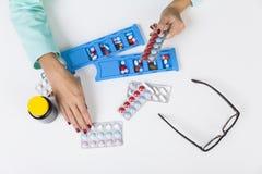 Γυναίκα με την κόκκινη στιλβωτική ουσία καρφιών στην τοποθέτηση των χαπιών στα κιβώτια Στοκ φωτογραφίες με δικαίωμα ελεύθερης χρήσης