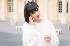 Γυναίκα με την κόκκινη χειλική συζήτηση στο smartphone στο Παρίσι, Γαλλία Γυναίκα με το κινητό τηλέφωνο λαβής τρίχας brunette Κορ στοκ εικόνες