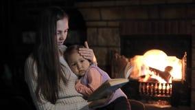 Γυναίκα με την κόρη στις περιτυλίξεις που κάθονται μπροστά από την εστία που διαβάζει ένα βιβλίο απόθεμα βίντεο