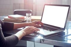 Γυναίκα με την ξανθή σύντομη εργασία αναλυτών τρίχας στο ομο-εργαζόμενο γραφείο στο lap-top, βιβλίο, φως της ημέρας Χέρια που δακ στοκ εικόνα με δικαίωμα ελεύθερης χρήσης