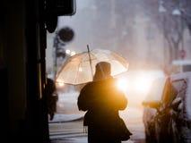 Γυναίκα με την ομπρέλα κάτω από το χιόνι στην πόλη Στοκ φωτογραφία με δικαίωμα ελεύθερης χρήσης