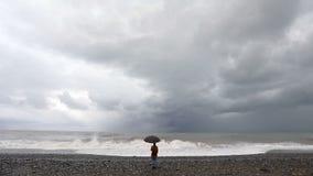Γυναίκα με την ομπρέλα κοντά στη θυελλώδη θάλασσα απόθεμα βίντεο