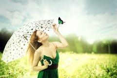 Γυναίκα με την ομπρέλα που περπατά αν και ένα παιχνίδι πάρκων με μια πεταλούδα Στοκ εικόνα με δικαίωμα ελεύθερης χρήσης
