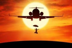 Γυναίκα με την ομπρέλα που πηδά κάτω από το αεροπλάνο Στοκ εικόνα με δικαίωμα ελεύθερης χρήσης