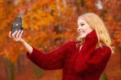 Γυναίκα με την παλαιά εκλεκτής ποιότητας κάμερα που παίρνει selfie τη φωτογραφία Στοκ Εικόνες