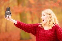 Γυναίκα με την παλαιά εκλεκτής ποιότητας κάμερα που παίρνει selfie τη φωτογραφία Στοκ φωτογραφία με δικαίωμα ελεύθερης χρήσης