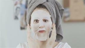 Γυναίκα με την πετσέτα στο κεφάλι που εφαρμόζει την καλλυντική ιαπωνική μάσκα στο πρόσωπό της και που κοιτάζει στον καθρέφτη φιλμ μικρού μήκους