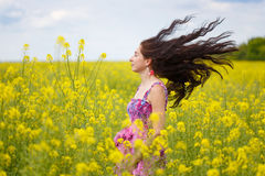 Γυναίκα με την πετώντας τρίχα στον κίτρινο τομέα βιασμών Στοκ εικόνα με δικαίωμα ελεύθερης χρήσης