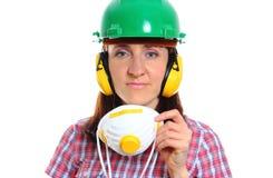 Γυναίκα με την προστατευτική μάσκα που φορά το κράνος και τα ακουστικά Στοκ Φωτογραφία