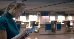 Γυναίκα με την ταμπλέτα από τους μετρητές εισόδου αερολιμένων φιλμ μικρού μήκους