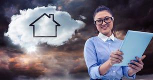 Γυναίκα με την ταμπλέτα και σύννεφο με το σπίτι ενάντια στο θυελλώδη ουρανό Στοκ Εικόνες