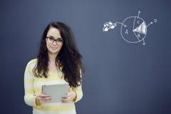 Γυναίκα με την ταμπλέτα μπροστά από το υπόβαθρο με το συρμένα επιχειρησιακά διάγραμμα και τα εικονίδια Στοκ φωτογραφία με δικαίωμα ελεύθερης χρήσης