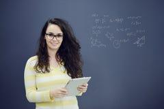 Γυναίκα με την ταμπλέτα μπροστά από το υπόβαθρο με το συρμένα επιχειρησιακά διάγραμμα και τα εικονίδια Στοκ Εικόνα