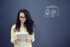 Γυναίκα με την ταμπλέτα μπροστά από το υπόβαθρο με το συρμένα επιχειρησιακά διάγραμμα και τα εικονίδια Στοκ εικόνα με δικαίωμα ελεύθερης χρήσης