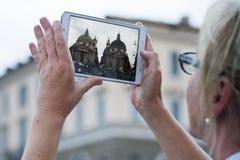 Γυναίκα με την ταμπλέτα που παίρνει την εικόνα στις δίδυμες εκκλησίες στοκ εικόνα με δικαίωμα ελεύθερης χρήσης