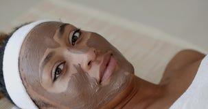 Γυναίκα με την του προσώπου μάσκα αργίλου στη SPA απόθεμα βίντεο