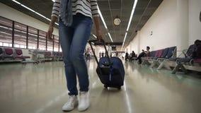 Γυναίκα με την τσάντα καροτσακιών που περπατά αργά στο τερματικό αερολιμένων φιλμ μικρού μήκους