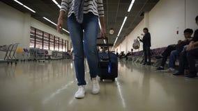Γυναίκα με την τσάντα καροτσακιών που περπατά αργά στο τερματικό αερολιμένων απόθεμα βίντεο