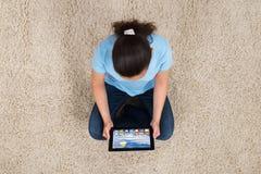 Γυναίκα με την ψηφιακή συνεδρίαση ταμπλετών στον τάπητα Στοκ Εικόνες