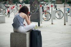 Γυναίκα με τη βαλίτσα που περιμένει το τραίνο με το smartphone μπροστά από το σταθμό τρένου στην πίσω άποψη Στοκ φωτογραφία με δικαίωμα ελεύθερης χρήσης