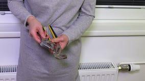 Γυναίκα με τη διευθετήσιμη έναρξη γαλλικών κλειδιών να δοκιμάσει την επισκευή τα θερμαντικά σώματα φιλμ μικρού μήκους